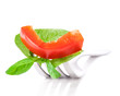 Bell pepper slice and leaf of basil on fork isolated on white ba