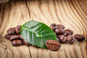 Coffee grains and green leaf on wooden background