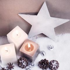 Stern und drei Kerzen auf Schnee