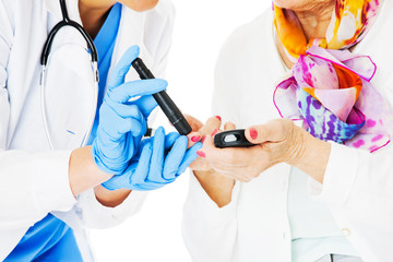 Doctor Examining Senior Woman's Blood Sugar Against White Backgr