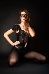 Beautiful girl in the masquerade mask on a black background.