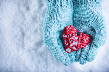 Female hands in light teal knitted mittens with entwined red hea