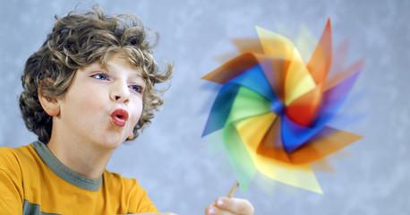 blonde child blowing a pinwheel