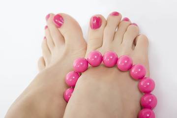 female foot with pink pedicure and accessory
