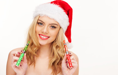 Beautiful woman in a Santa hat with e-cigarettes