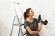 Young beautiful brunette woman sitting on a ladder with a drill