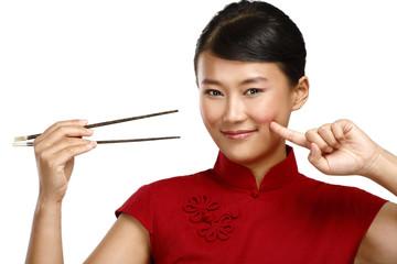 Chinese woman showing asian food using chopstick