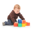 Little kid playing with toy blocks on a white background.
