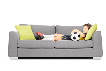 Boy in sportswear with a soccer ball sleeping on a modern sofa