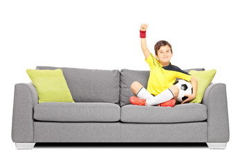 Happy boy with a soccer ball on a sofa and gesturing happiness