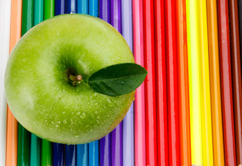 Colored pencils and a green apple