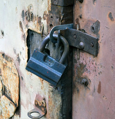 the mechanical  hinged lock on old crumpled of a door of garage