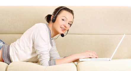 A lying woman on a sofa with a laptop and a headset indoors