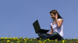 Teenage girl using laptop and headphones outdoors