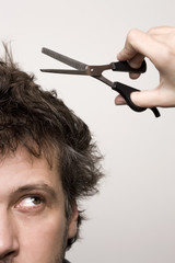 Closeup of worried man`s face, scissors and hair