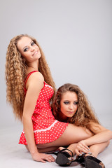 Two girls twins, isolated on the grey background