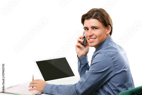 Happy business man on cell phone in front of laptop