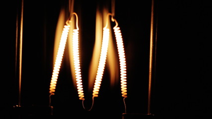 Light bulb flickering. Incandescence thread, close up.