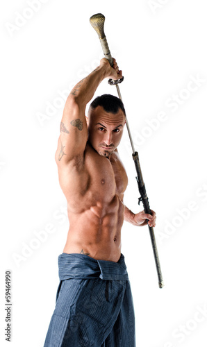 Muscular shirtless man with traditional martial arts sword