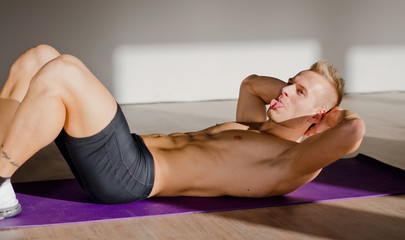 Shirtless young man sticking tongue out while training abs