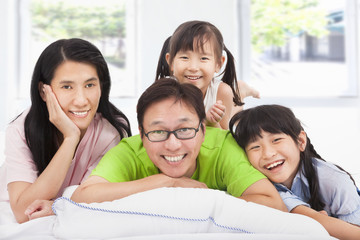 Happy asian  family on the bed