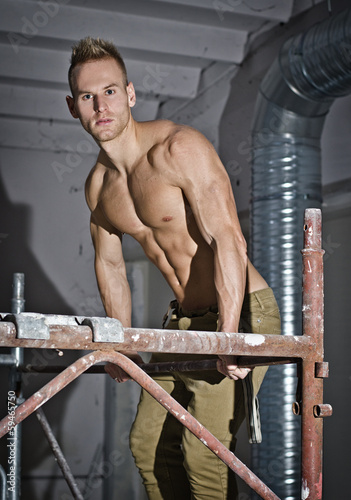 Muscular young construction worker climbing scaffolding
