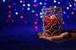 Candle in hand on blur lights background