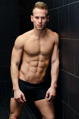 Muscular young man shirtless leaning against tiled wall