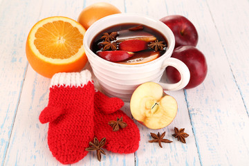 Fragrant mulled wine in bowl on wooden table close-up