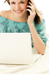 A young woman with a laptop talking on the phone.
