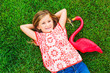 Smiling little girl lying on green grass with pink flamingo