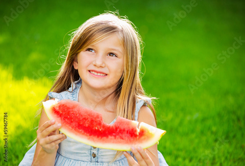 Cute little girl eating watermelon