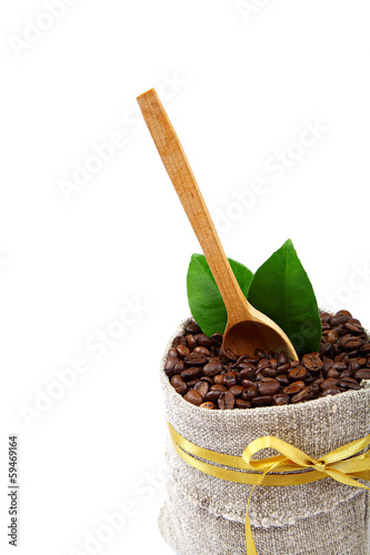 Coffee beans in a canvas bag and a wooden spoon.