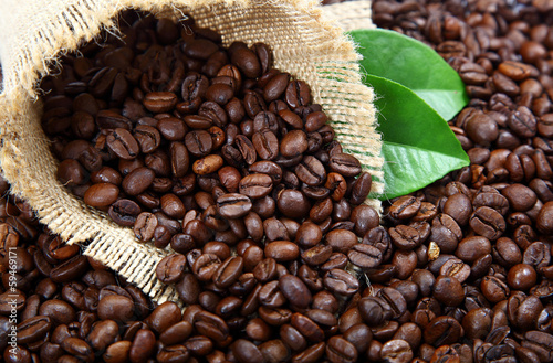 Coffee beans in a bag and green leaves .