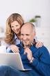 paar schaut lachend auf laptop