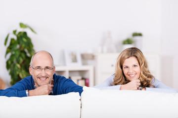 lachendes paar schaut über das sofa
