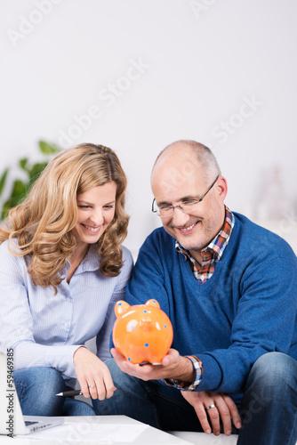 glückliches ehepaar schaut auf sparschwein