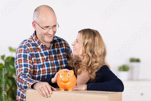 zufriedenes paar mit sparschwein und umzugskarton