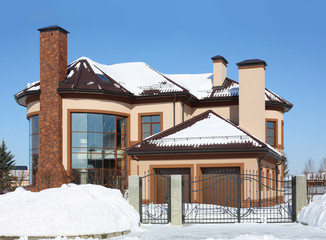 Modern rounded cottage with iron gates at frosty