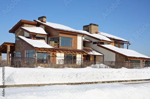 Modern brown cottage and snowdrift at frosty and sunny winter