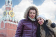 Young man and woman stand near Spasskaya tower on Red Square