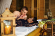 Beautiful woman and young man lie on bamboo bed and look