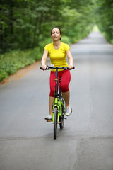 Beautiful woman in sport clothes rides bicycle in park at summer