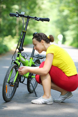 Young woman in sport clothes repairs bike in park at summer day.