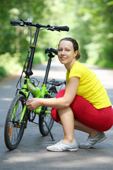 Young woman in sport clothes sits near bike and smiles in park