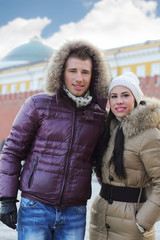Young man and woman in warm clothes stand at street at winter