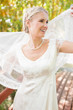 Pretty smiling blonde bride holding her veil out