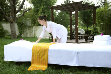 Maid making massage table outdoors