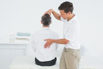 Male chiropractor examining mature man