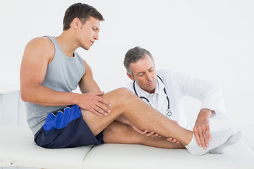 Side view of a young man getting his leg examined